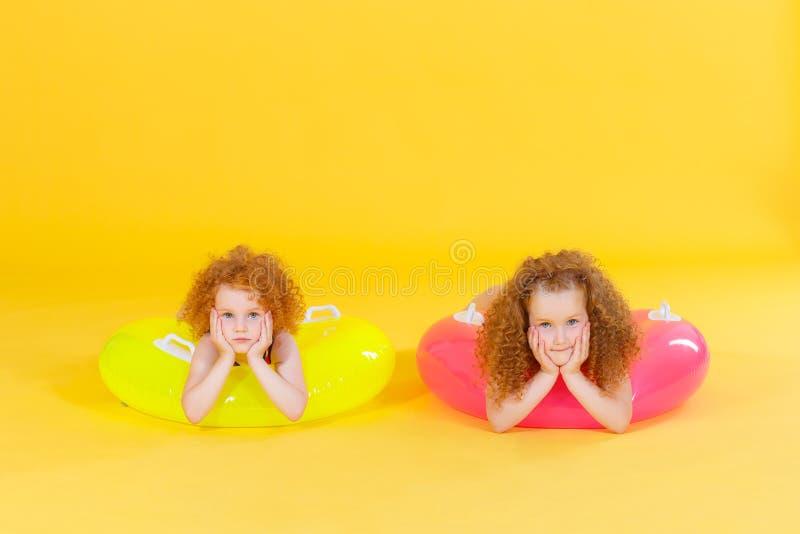 Lustige glückliche Kinder mit schwimmendem Kreis auf einem farbigen Hintergrund Seashells gestalten auf Sandhintergrund Babyspaß  stockfoto