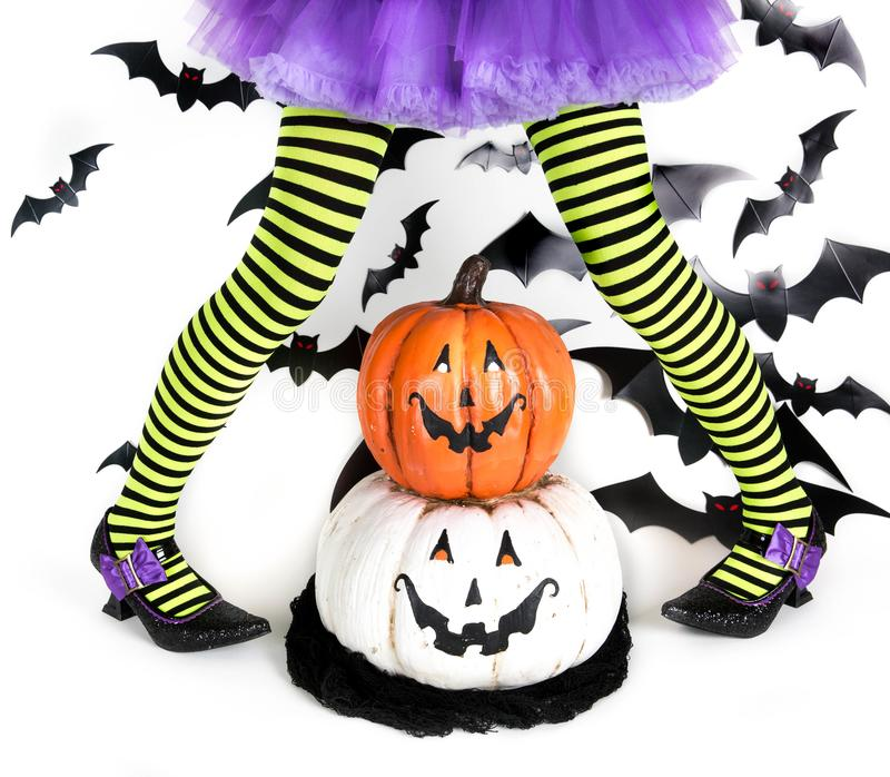 Lustige grüne schwarze gestreifte Beine eines kleinen Mädchens mit Halloween-Kostüm einer Hexe mit Hexenschuhen und smileyhallowe stockfotografie