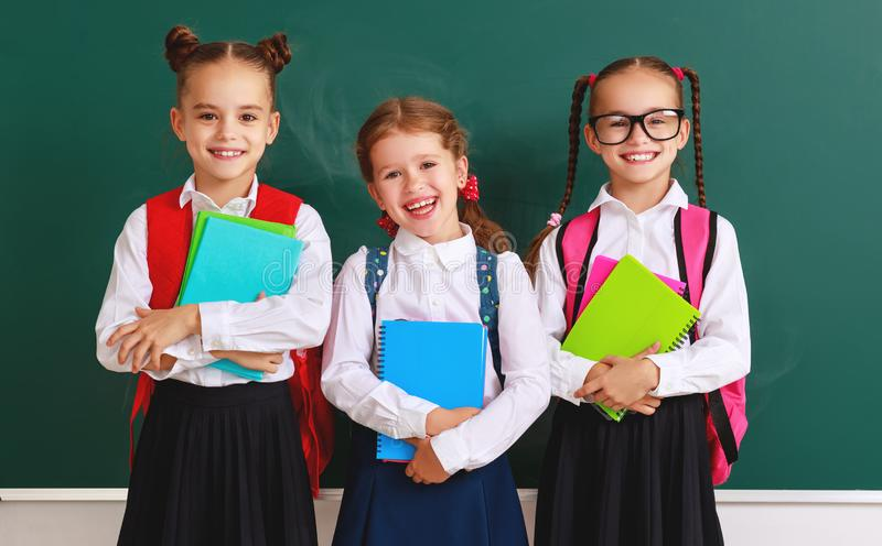 Lustige Gruppenkinder Schüler und Schulmädchen, Studentenjunge und Mädchen über Schultafel lizenzfreie stockfotografie