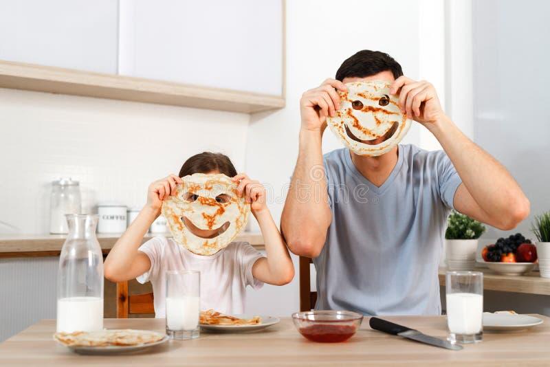 Lustige hübsche Tochter und Vater machen Gesichter mit Pfannkuchen, machen Spaß zusammen an der Küche während der Wochenenden, ge lizenzfreie stockbilder