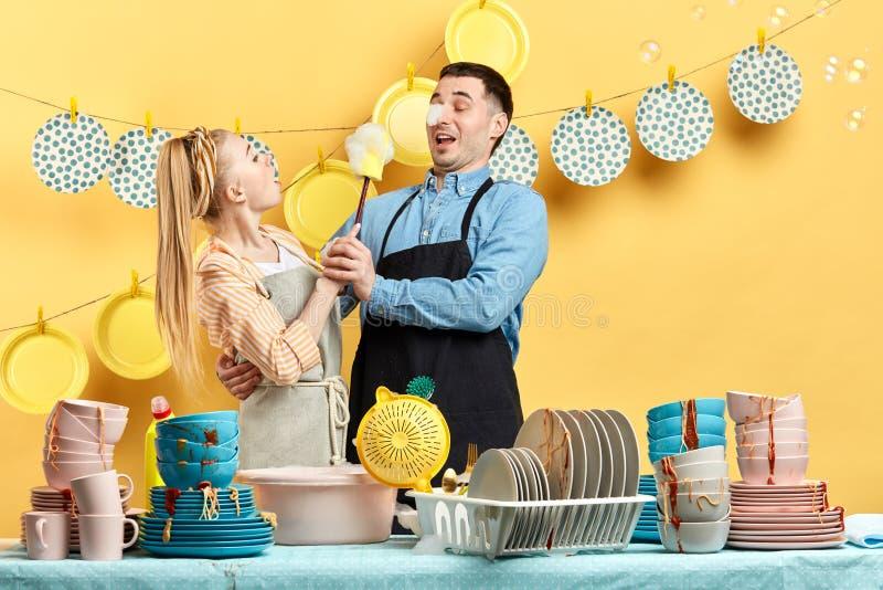 Lustige Hausfrau, die versucht, ihren Ehemann in der Küche zu waschen lizenzfreie stockfotos