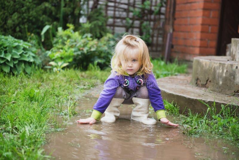 Lustige 2 Jahre alte Baby, die in der Pfütze spielen. lizenzfreie stockbilder
