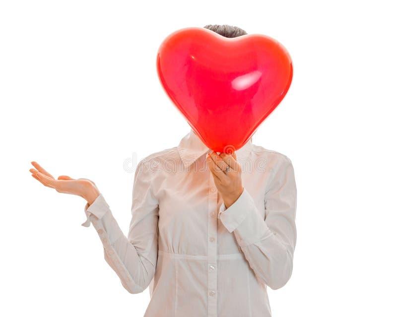 Lustige junge Brunettefrau mit dem roten Herzen bei der Handaufstellung lokalisiert auf weißem Hintergrund Heilig-Valentinsgruß ` lizenzfreies stockfoto