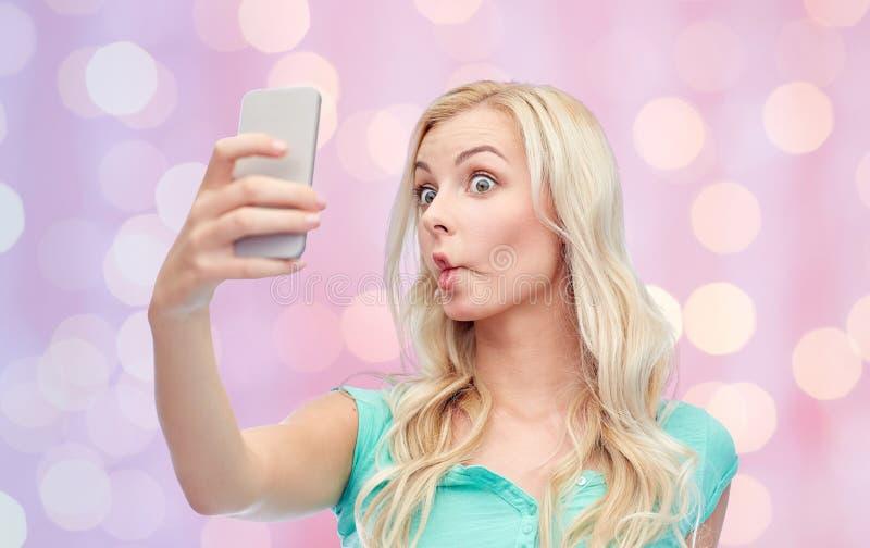 Lustige junge Frau, die selfie mit Smartphone nimmt stockbild
