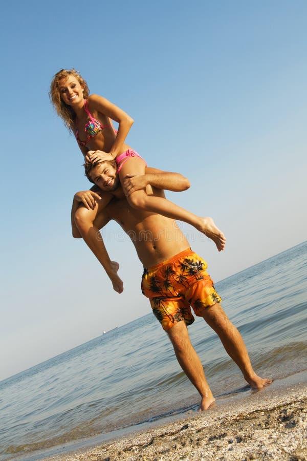 Lustige junge Paare auf der Küste stockfoto