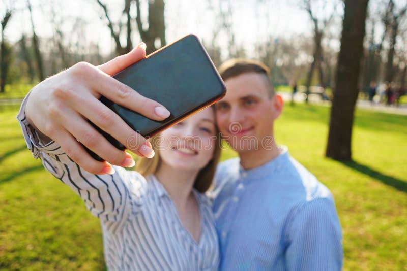 Lustige junge Paare haben die schöne Zeit zusammen und gehen im Park lizenzfreie stockbilder