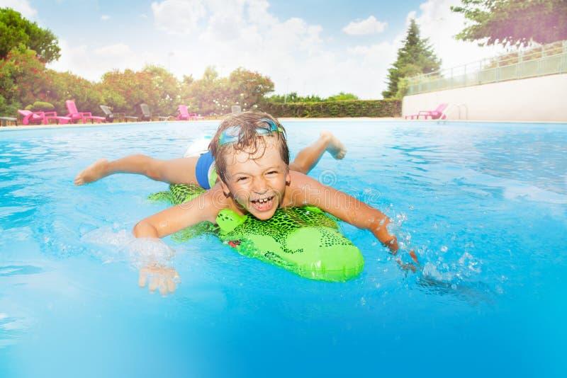 Lustige Jungenschwimmen mit aufblasbarem Krokodil stockbilder