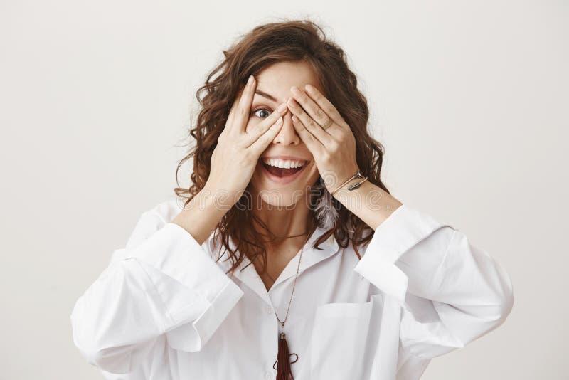Lustige kaukasische weibliche Bedeckung mustert mit den Händen beim Spähen und Lächeln und ist in der spielerischen Stimmung und  lizenzfreies stockfoto
