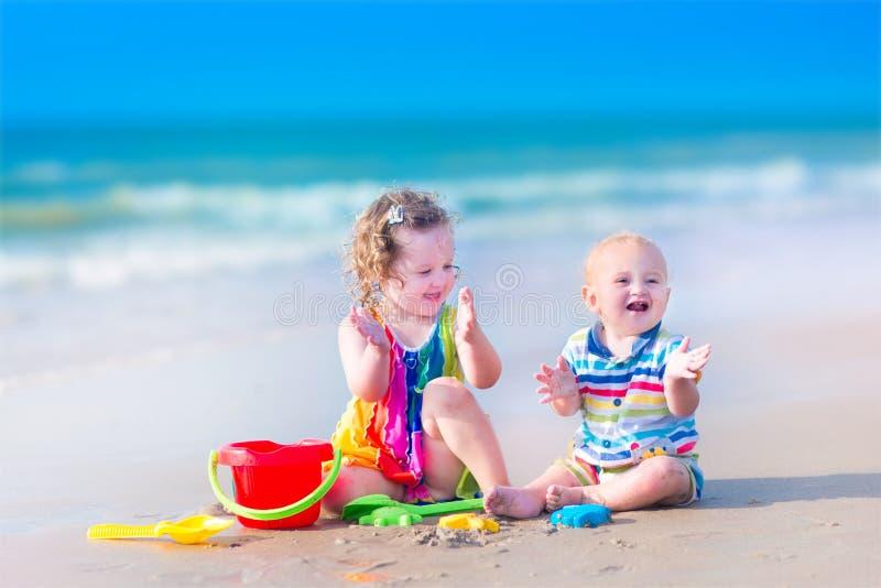 Lustige Kinder, die auf dem Strand spielen lizenzfreies stockfoto