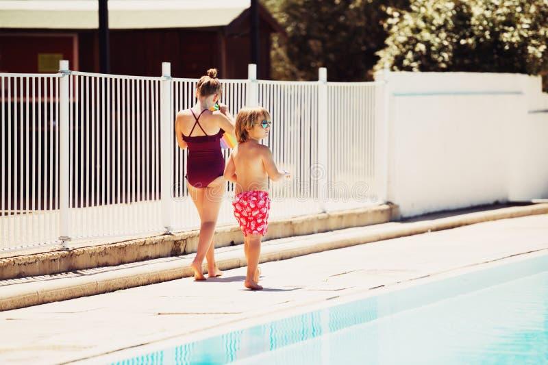Lustige Kinder, die durch das Pool spielen stockbilder