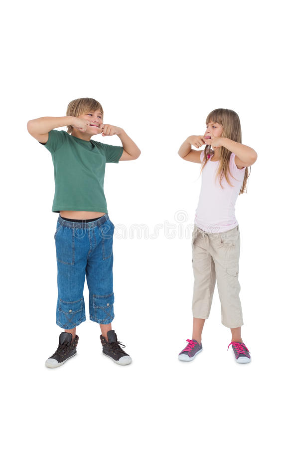 Lustige Kinder, die Gesichter ziehen und einander betrachten lizenzfreie stockfotos