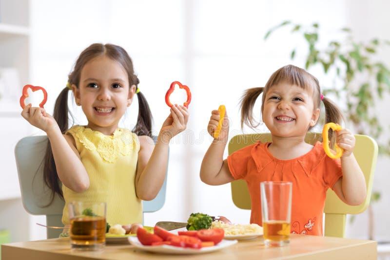Lustige Kinder, die im Kindergarten spielen und essen stockbild