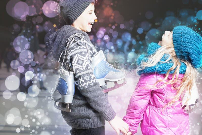 Lustige Kinder, die Schlittschuhschuhe an der Eisbahn im Freien halten stockfoto