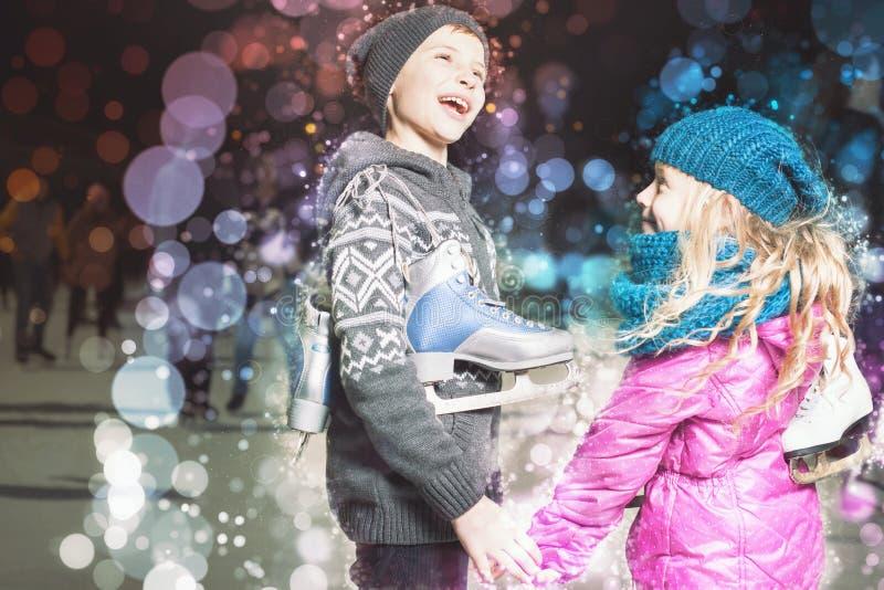 Lustige Kinder, die Schlittschuhschuhe an der Eisbahn im Freien halten lizenzfreies stockbild