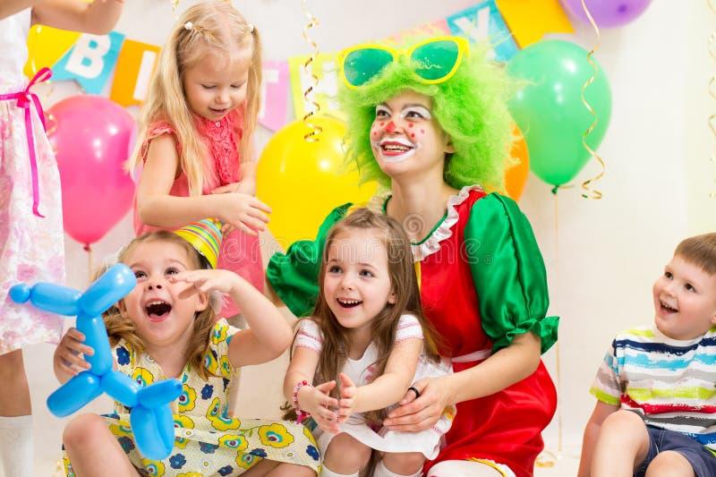 Lustige Kinder mit Clown auf Geburtstagsfeier lizenzfreie stockfotos
