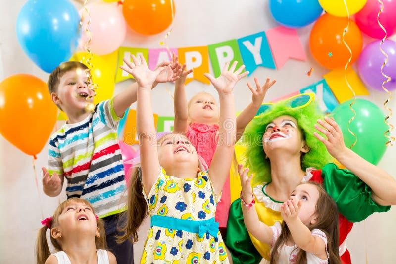 Lustige Kindergruppe mit dem Clown, der Geburtstag feiert stockbild