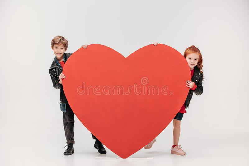 lustige Kleinkinder verbinden das Verstecken hinter großem rotem Herzen stockbild