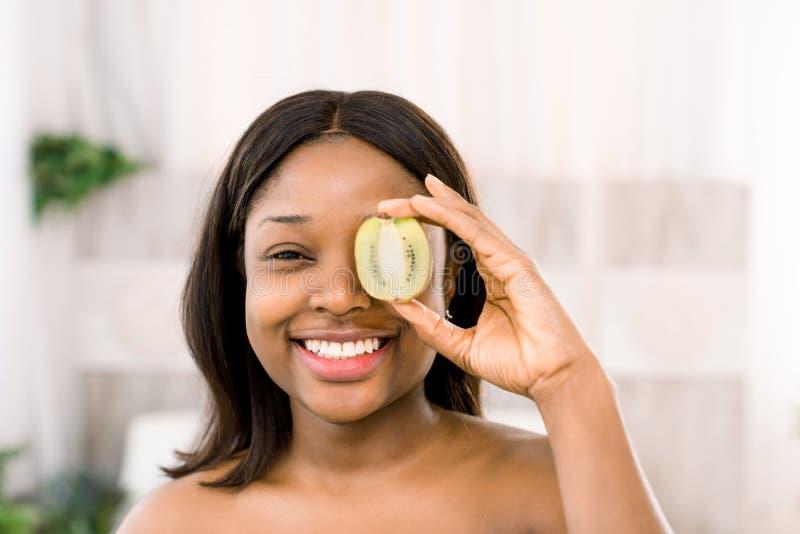 Lustige lächelnde Holdingkiwihälfte der jungen Frau des Afroamerikaners vor ihrem Auge über weißem Hintergrund lizenzfreie stockbilder