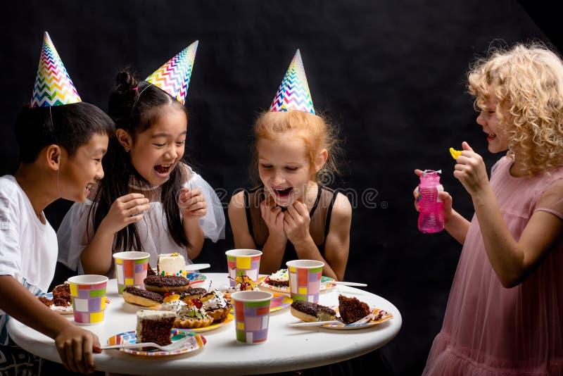 Lustige lachende Kinder betrachten die bursted Blasen stockfotos