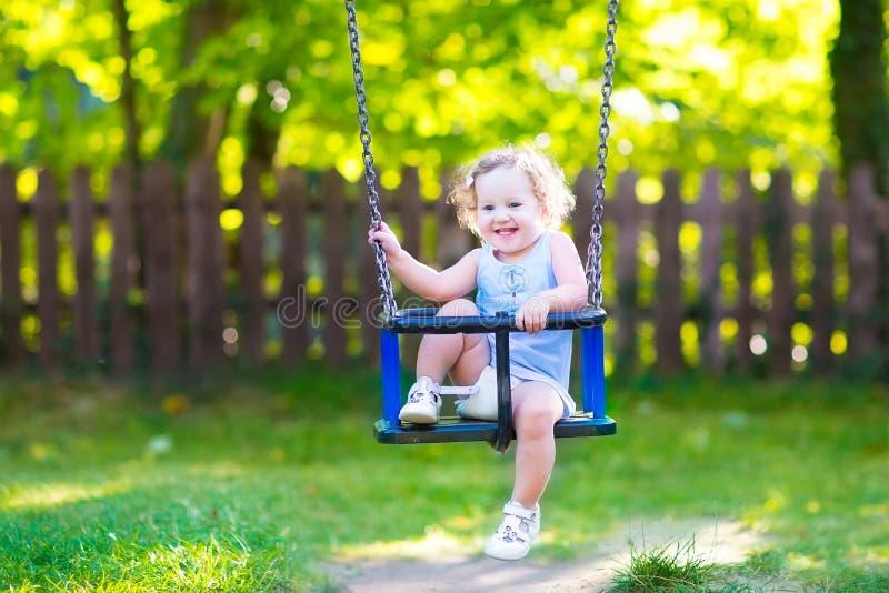 Lustige lachende Kleinkindmädchenschwingfahrt auf Spielplatz lizenzfreies stockbild