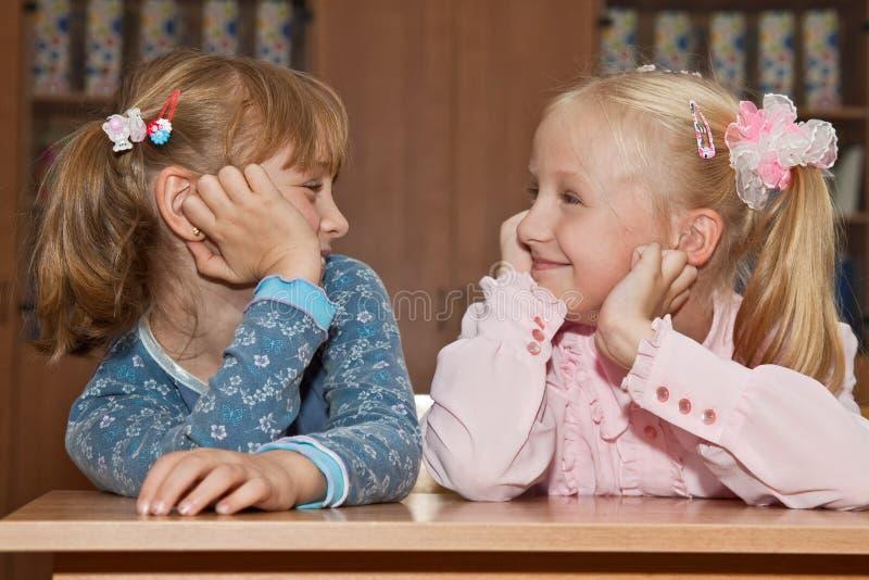 Lustige Mädchen in der Schule am Schreibtisch stockbild