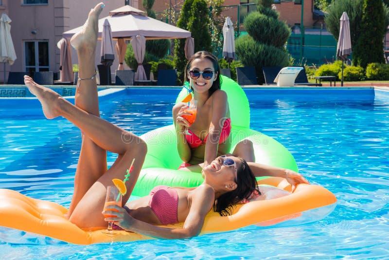 Lustige Mädchen, die auf Luftmatraze im Swimmingpool liegen lizenzfreies stockbild