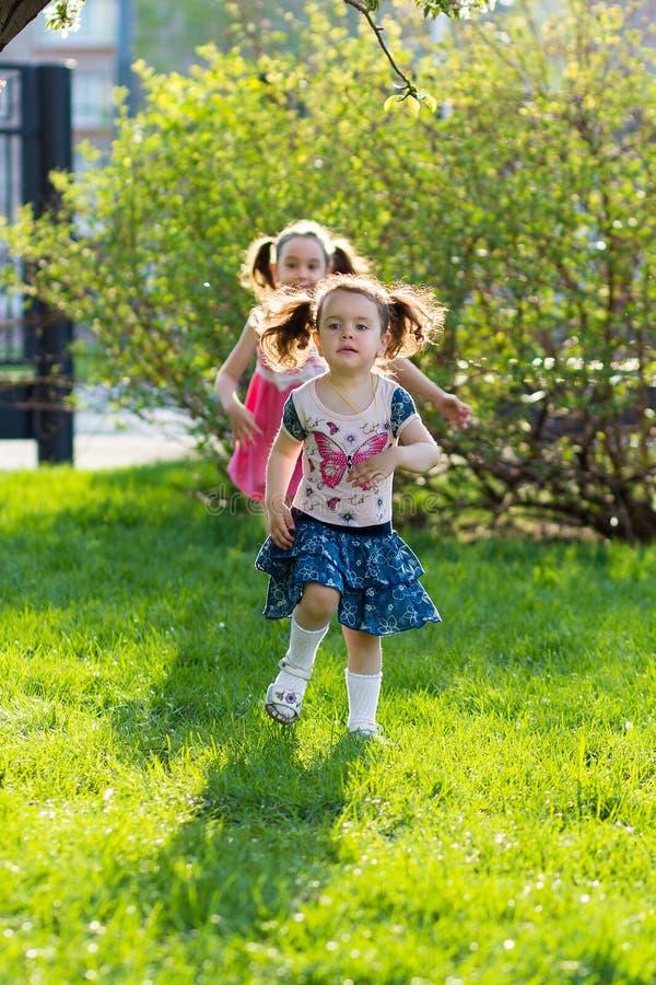 Lustige M?dchen, die auf den Rasen mit ihrer Mutter gehen Schwestern spielen zusammen mit Mutter M?tterliche Sorgfalt Gl?ckliche  stockfotos