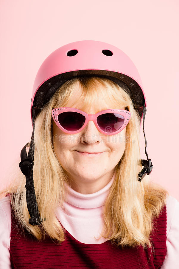 Lustige Frau tragender einen.Kreislauf.durchmachensturzhelmporträt-Rosahintergrund wirklich lizenzfreie stockbilder