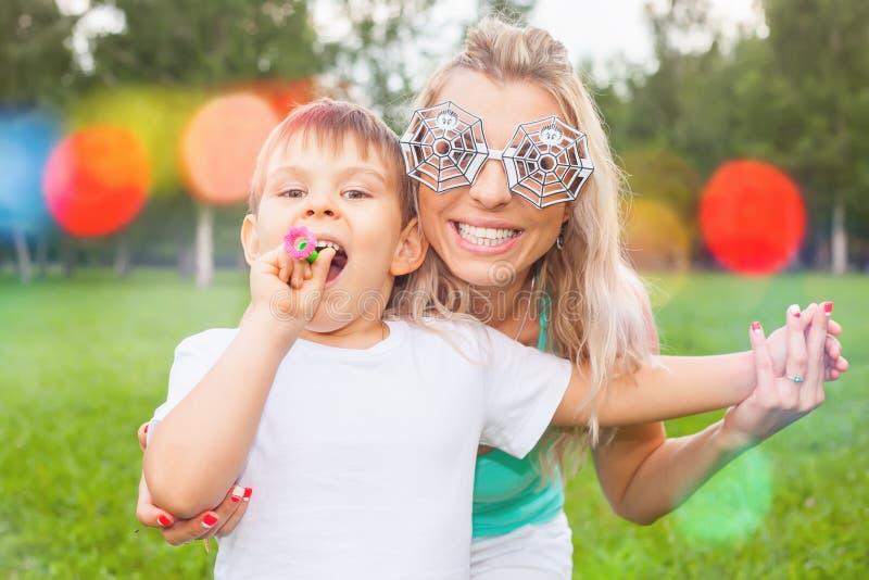 Lustige Mutter mit Kind dem im Freienhat eine Parteizeit lizenzfreies stockfoto