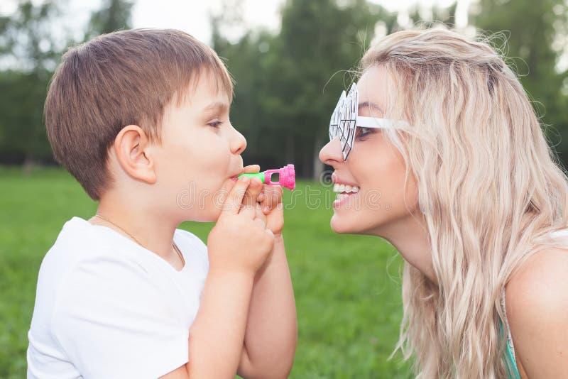Lustige Mutter mit Kind dem im Freienhat eine Parteizeit lizenzfreie stockfotos