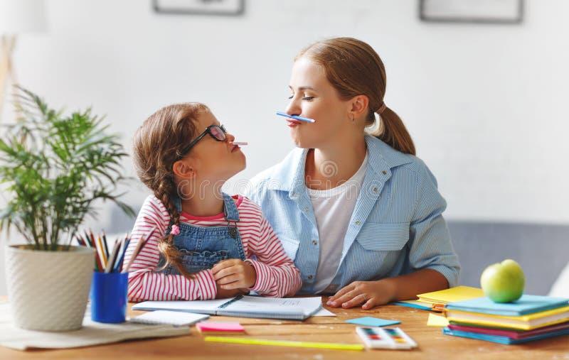 Lustige Mutter- und Kindertochter, die Hausarbeit Schreiben und readi tut stockfotografie