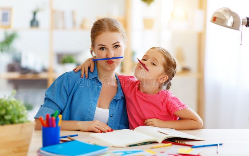 Lustige Mutter- und Kindertochter, die Hausarbeitschreiben und -ablesen tut stockbilder