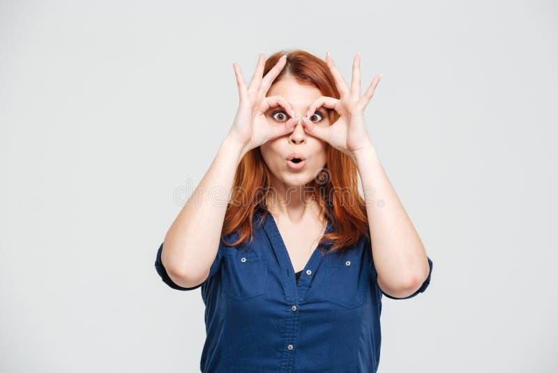Lustige nette junge Frau, die throug Gläser gemacht von den Fingern schaut stockfotos