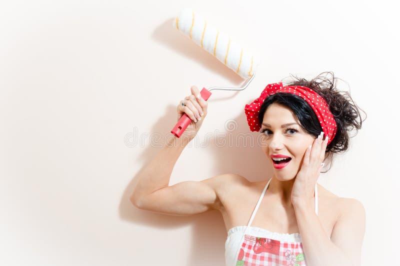 Lustige reizend junge Brunettefrau schöne Pinupmädchen-Farbenwand mit dem glücklichen Lächeln der Rollenplatte stockbild