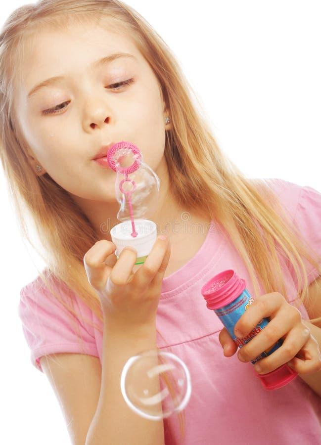 Lustige reizende Schlagseifenblasen des kleinen Mädchens lizenzfreie stockfotos