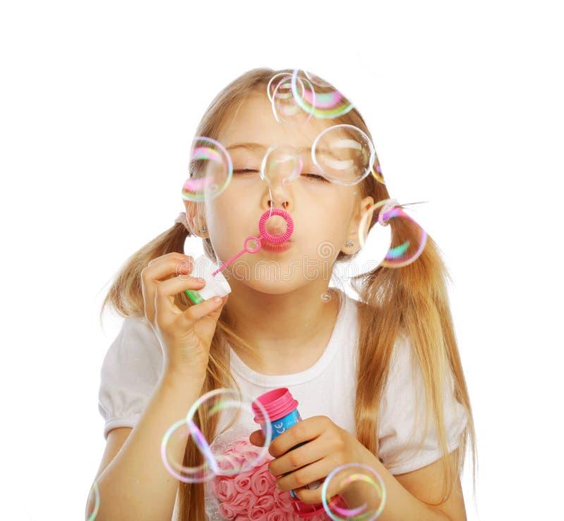 Lustige reizende Schlagseifenblasen des kleinen Mädchens stockfoto