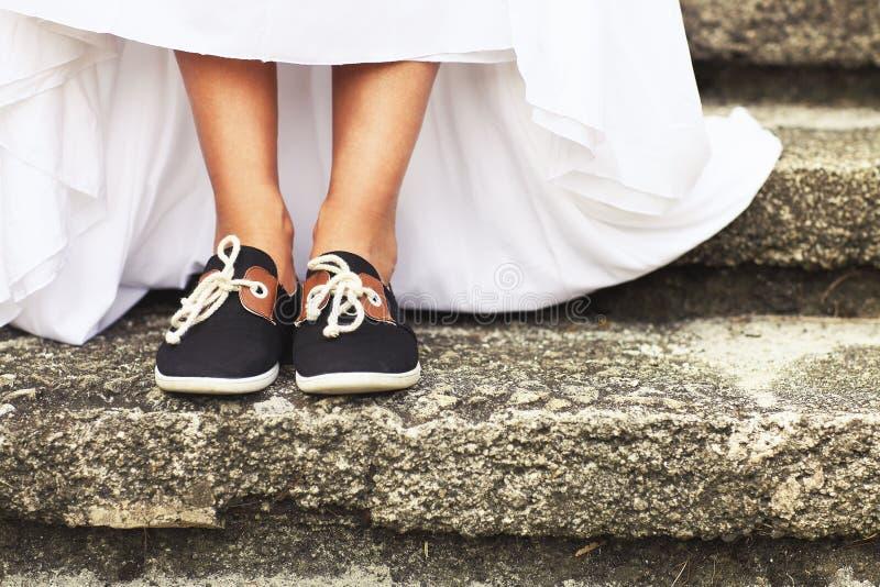Lustige schöne Braut, die blaue Laufschuhe trägt stockfotografie