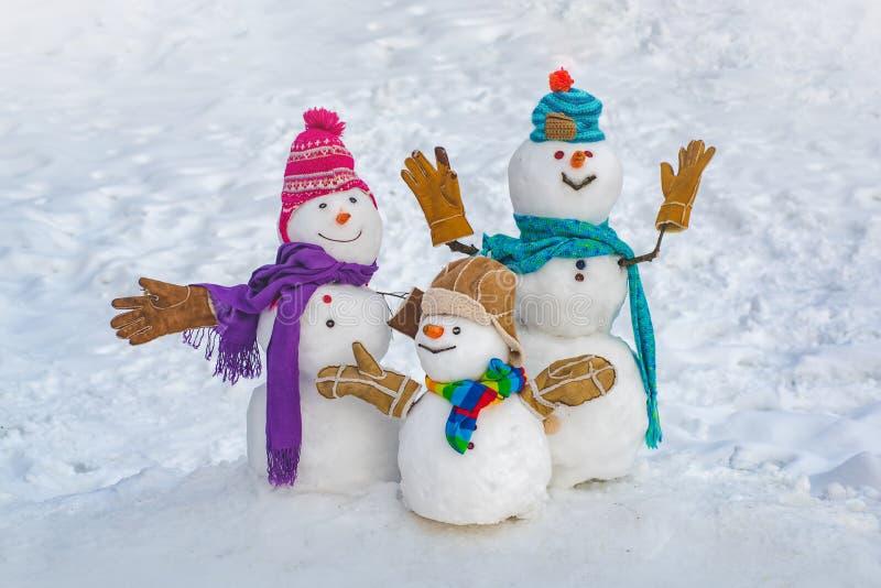 Lustige Schneemannfamilie im stilvollen Hut und im Schal auf schneebedecktem Feld Gl?ckliche Winterzeit Gl?cklicher lustiger Schn stockbilder