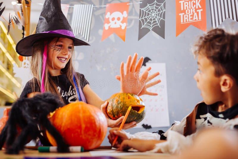 Lustige Schwester, die Halloween-Kostüm erschrickt Bruder mit Handplätzchen trägt lizenzfreies stockfoto