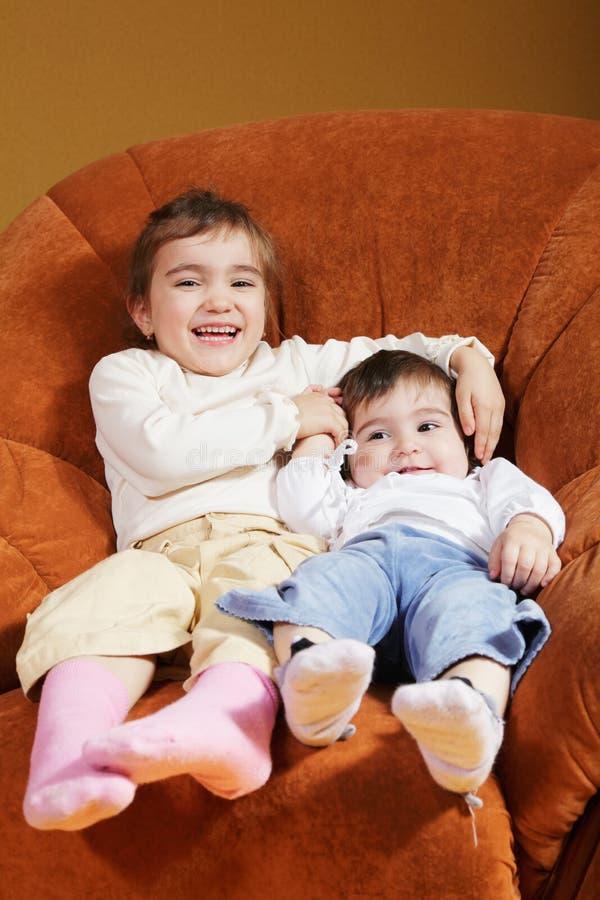 Lustige Schwestern, die im Stuhl sitzen stockfotos