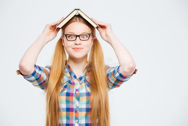 Lustige Studentin mit Buch auf Kopf stockbild