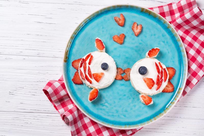 Lustige Toast in einer Form von Fische, Käse des Sandwiches und Beeren, Nahrung mit Sahne küssen für Kinder Idee, Draufsicht lizenzfreies stockbild