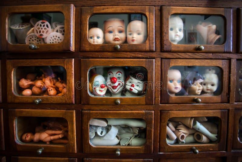 Lustige und h?ssliche Gesichter von Puppen innerhalb des Holzhauses mit kleinen Fenstern Viele Teile K?pfe und Beine innerhalb de stockfotos