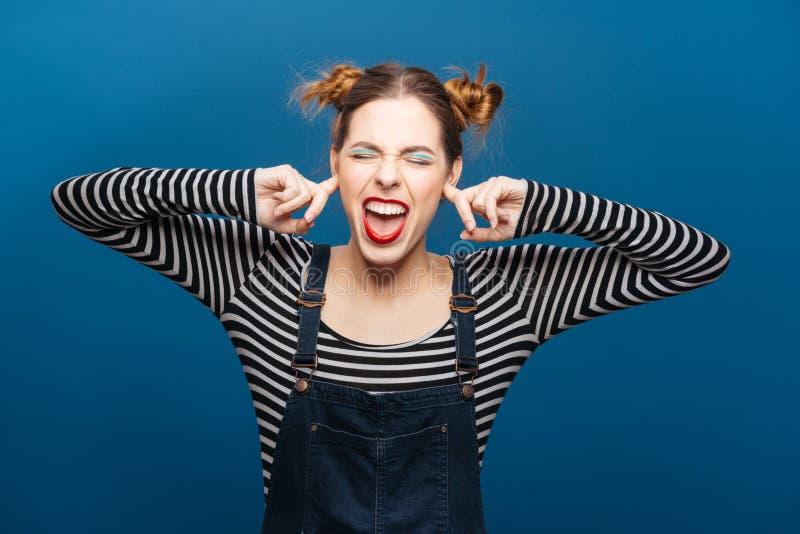 Lustige verärgerte Frau mit geschlossenen Augen bedeckte Ohren durch Finger lizenzfreie stockfotos