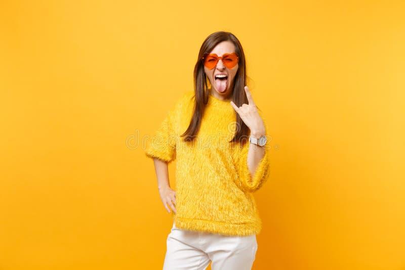 Lustige verrückte junge Frau in der Pelzstrickjacke und in den orange Gläsern Schreien des Herzens, das Stein-nrollenzeichen zeig lizenzfreie stockfotos