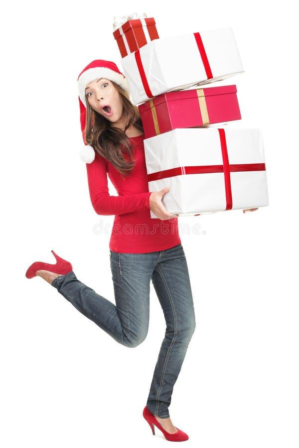 Lustige Weihnachtsfrau in der Hast, die mit Geschenken läuft stockfotografie