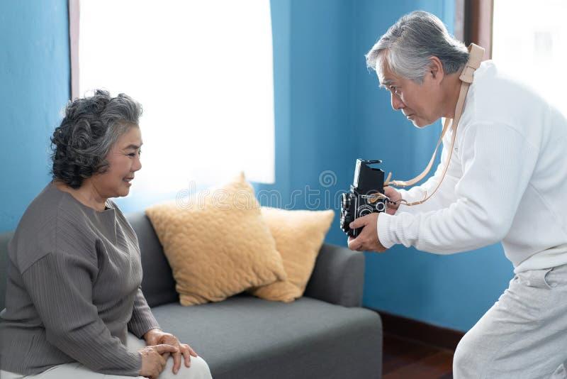 Lustige Zeit! Reifer Mannphotograph, der den Spaß spielt hat, Foto von künstlerischem seine Frau zu Hause machend Foto für Gedäch lizenzfreies stockfoto
