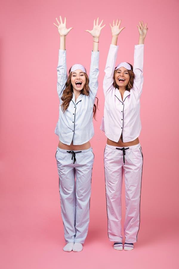 Lustige zwei Freundinnen in den Pyjamas lokalisiert über rosa Hintergrund lizenzfreie stockbilder