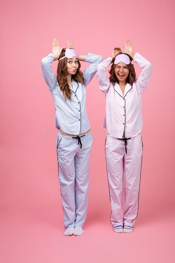 Lustige zwei Freundinnen in den Pyjamas lokalisiert über rosa Hintergrund stockbild