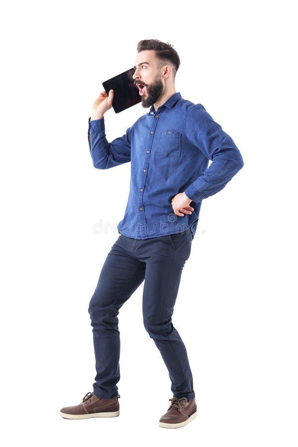 Lustiger bärtiger Geschäftsmann, der auf übergroßem großem Handy- oder Tablettenkonzept schreit lizenzfreies stockfoto